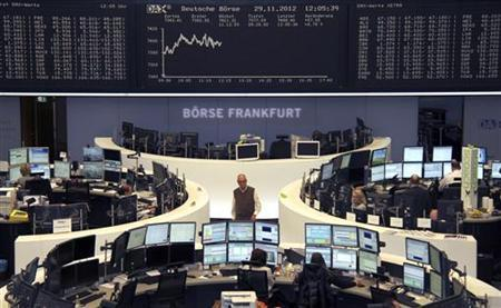 Traders are pictured at their desks in front of the DAX board at the Frankfurt stock exchange November 29, 2012. REUTERS/Remote/Lizza David (GERMANY - Tags: BUSINESS)