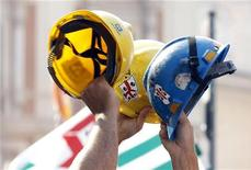 Operai sollevano gli elmetti durante una protesta sindacale per il lavoro. REUTERS/Alessandro Bianchi