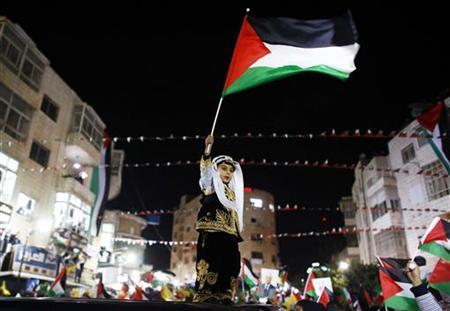 A Palestinian boy in traditional clothes waves a Palestinain flag during a rally in the West Bank city of Ramallah November 29, 2012. Palestinian President Mahmoud Abbas appealed to the U.N. General Assembly to recognize Palestinian statehood by supporting a resolution to upgrade the U.N. observer status of the Palestinian Authority from ''entity'' to ''non-member state.'' REUTERS/Marko Djurica