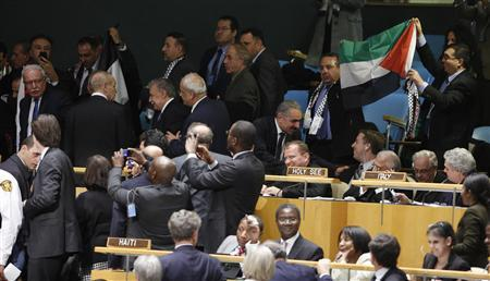 Palestinian supporters cheer and wave a flag as members of their delegation are whisked away by security after the vote during a meeting at UN Headquarters, in New York, November 29, 2012. The 193-nation U.N. General Assembly overwhelmingly approved a resolution on Thursday to upgrade the Palestinian Authority's observer status at the United Nations from ''entity'' to ''non-member state,'' implicitly recognizing a Palestinian state. REUTERS/Chip East
