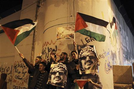 Palestinians hold posters with an image of the late Palestinian leader Yasser Arafat and wave Palestinian flags during a rally opposite to part of Israel's controversial barrier in the West Bank city of Bethlehem November 29, 2012. REUTERS/Ammar Awad
