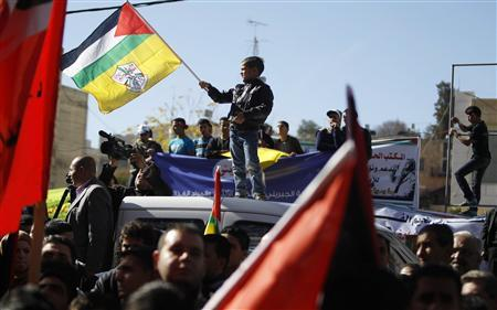 A Palestinian boy holds a flag as he stands atop a car during a rally in the West Bank city of Hebron, supporting the resolution that would change the Palestinian Authority's United Nations observer status from ''entity'' to ''non-member state'' November 29, 2012. REUTERS/Ammar Awad