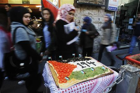 People look at a pizza displayed outside a restaurant, with toppings arranged to depict a Palestinian flag, in the West Bank city of Ramallah November 29, 2012. The U.N. General Assembly is set to implicitly recognize a sovereign state of Palestine on Thursday despite threats by the United States and Israel to punish the Palestinian Authority by withholding much-needed funds for the West Bank government. REUTERS/Mohamad Torokman