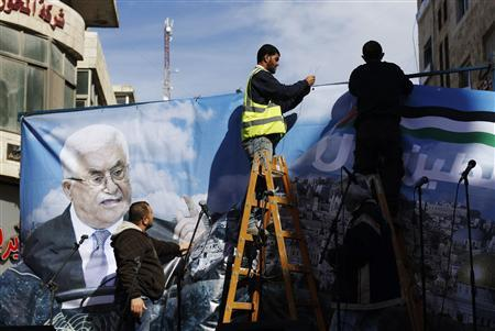 Labourers put up a banner depicting Palestinian President Mahmoud Abbas before a rally in the West Bank city of Ramallah, supporting the resolution that would change the Palestinian Authority's United Nations observer status from ''entity'' to ''non-member state,'' November 29, 2012. The U.N. General Assembly is set to implicitly recognize a sovereign state of Palestine on Thursday despite threats by the United States and Israel to punish the Palestinian Authority by withholding much-needed funds for the West Bank government. REUTERS/Mohamad Torokman