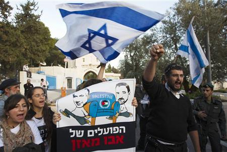 Israeli ultranationalist right-wing protesters hold a placard depicting Prime Minister Benjamin Netanyahu (L) and Foreign Minister Avigdor Lieberman during a demonstration against the Palestinian Authority's efforts to secure a diplomatic upgrade at the United Nations, outside the U.N. offices in the West Bank village of Jabel Mukaber, near Jerusalem November 29, 2012. The U.N. General Assembly is set to implicitly recognize a sovereign state of Palestine on Thursday despite threats by the United States and Israel to punish the Palestinian Authority by withholding much-needed funds for the West Bank government. The placard reads, '' Mahmoud Abbas' workers'' REUTERS/Ronen Zvulun