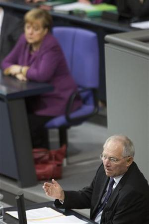 German Finance Minister Wolfgang Schaeuble delivers a government policy statement as German Chancellor Angela Merkel (rear) sits on the government bench at Germany's lower house of parliament, the Bundestag, before the house votes on financial help for Greece, in Berlin November 30, 2012. REUTERS/Thomas Peter (GERMANY - Tags: POLITICS BUSINESS)