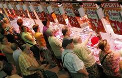 La tasa interanual del indicador adelantado del índice de precios al consumo (IPC) de España bajó drásticamente en noviembre debido a la bajada de los precios de los carburantes y lubricantes, según datos divulgados el viernes el Instituto Nacional de Estadística (INE). En la imagen de archivo, un grupo de personas hace cola para comprar en una carnicería de Barcelona, el 1 de septiembre de 2012. REUTERS/Albert Gea