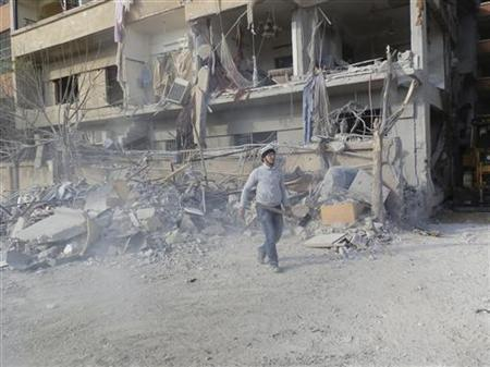 A man carrying a shovel, walks near buildings damaged after what activists said was a Syrian Air Force fighter jet operated by those loyal to Syria's President Bashar al-Assad, fired missiles in Daria, near Damascus November 29, 2012. REUTERS/Kenan Al-Derani/Shaam News Network/Handout