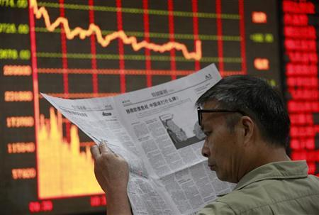 An investor reads a newspaper in front of an electrical board showing stock information at a brokerage house in Huaibei, Anhui province September 19, 2011. REUTERS/Stringer/Files