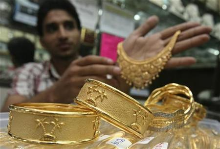 A salesman displays gold ornaments at a jewellery showroom in Chandigarh June 8, 2010. REUTERS/Ajay Verma/Files