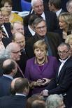 El parlamento alemán ha aprobado por amplia mayoría el viernes un paquete de medidas destinadas a reducir la carga de deuda de Grecia al 124 por ciento del PIB para el año 2020. En la imagen, la canciller Angela Merkel y varios parlamentarios antes de la votación en el Bundestag, Berlín, el 30 de noviembre de 2012. REUTERS/Thomas Peter