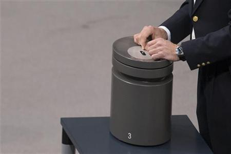 An usher rests his hands on a ballot box before a vote on financial help for Greece at the lower house of parliament, the Bundestag in Berlin, November 30, 2012. REUTERS/Thomas Peter (GERMANY - Tags: POLITICS BUSINESS)