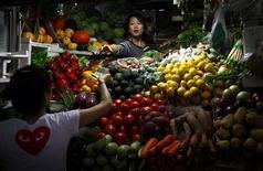 """Vendedora de legumes recebe pagamento de cliente em Mercado no centro de Pequim. Os preços globais de alimentos permaneceram estáveis, ainda que perto dos níveis recordes de 2008, afirmou o Banco Mundial, ao alertar que uma """"nova norma"""" de alimentos mais caros está ameaçando elevar a fome e desnutrição nas regiões mais pobres. 01/06/2012 REUTERS/David Gray"""