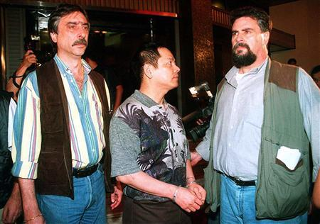 Wan Kuok-koi (C), alias Broken Tooth Koi, one of the most powerful Chinese Mafia leaders in Asia, is seen handcuffed after being arrested by Macau's top crime-fighter, Judicial Police Director Antonio Marques Baptista (R) during an anti-crime raid in Macau, in this file picture taken May 1, 1998. REUTERS/Stringer