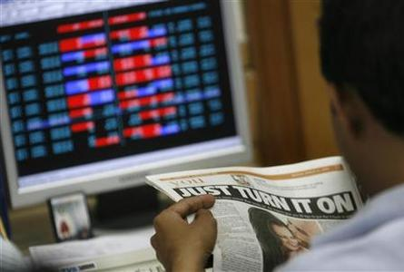 A broker reads a newspaper while trading at a stock brokerage firm in Mumbai March 31, 2008. REUTERS/Arko Datta/Files
