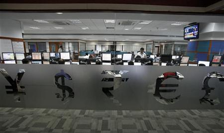 Foreign currency traders work inside a trading firm behind the signs of various world currencies, in Mumbai May 24, 2012. REUTERS/Vivek Prakash/Files