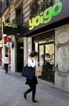 El operador de telefonía móvil Yoigo, controlado por TeliaSonera, se ha sumado a la guerra de precios en el negocio de la telefonía móvil en España, recortando sus tarifas en más de un 20 por ciento y retomando la subvención de los terminales. En la imagen de archivo, una mujer habla por teléfono minetras pasa junto a una tienda de Yoigo en Madrid, el 26 de abril de 2011. REUTERS/Andrea Comas