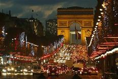 Christmas holiday lights hang from trees to illuminate Champs Elysees in Paris as rush hour traffic fills the avenue leading up to the Arc de Triomphe November 22, 2012. REUTERS/Charles Platiau