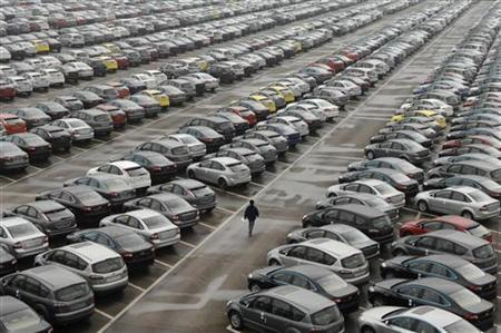 An employee walks past new cars at the parking lot of Changan Ford Mazda Automobile Co. Ltd, Ford Motor's joint venture in China, in Chongqing Municipality, October 12, 2010. REUTERS/Stringer