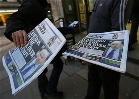 A man takes a copy of an evening newspaper, which features an article about Lord Justice Brian Leveson's report on media practices on its front page, in central London November 29, 2012 REUTERS/Olivia Harris