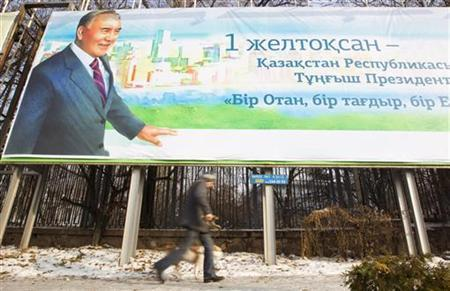 A man walks with a dog past a poster depicting Kazakh President Nursultan Nazarbayev to mark the inaugural Day of the First President, in Almaty November 28, 2012. REUTERS/Shamil Zhumatov