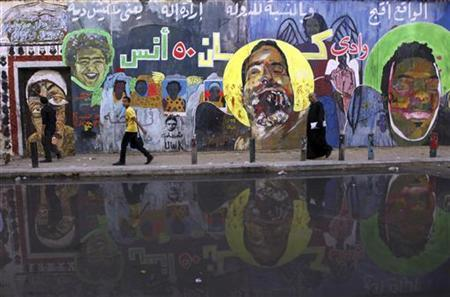 People walk past murals showing protesters killed during clashes with police in 2011 according to information written on the wall, at Mohamed Mahmoud street in Cairo November 29, 2012. REUTERS/Amr Abdallah Dalsh