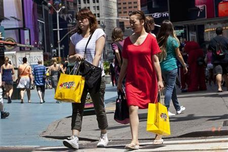 Women carry shopping bags through Times Square in New York, July 27, 2012. REUTERS/Andrew Burton