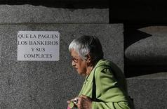 El Gobierno ha decidido no actualizar las pensiones de acuerdo con la inflación registrada en 2012, y ha anunciado un cambio en la ley vigente para poder recurrir al fondo de reserva de la Seguridad Social y hacer frente al pago extra de Navidad de las pensiones. En la imagen del pasado mes de octubre, una mujer pasa ante un cartel de protesta contra la crisis en Madrid. REUTERS/Juan Medina