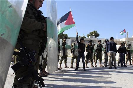 A Palestinian youth (C) waves a flag in front of Israeli soldiers during a demonstration in the West Bank village of al-Masara near Bethlehem, marking the recognition of a sovereign Palestinian state by the United Nations November 30, 2012. The 193-nation U.N. General Assembly on November 29 overwhelmingly approved the de facto recognition of the sovereign state of Palestine after Palestinian President Mahmoud Abbas called on the world body to issue its long overdue ''birth certificate.'' REUTERS/Ammar Awad