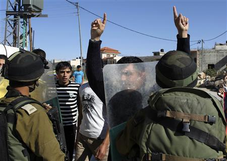 A Palestinian protester (C) gestures in front of Israeli soldiers during a demonstration in the West Bank village of al-Masara near Bethlehem, marking the recognition of a sovereign Palestinian state by the United Nations November 30, 2012. REUTERS/Ammar Awad