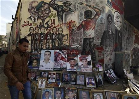 A man walks past photos showing people killed during protests, at Mohamed Mahmoud street in Cairo November 29, 2012. REUTERS/Amr Abdallah Dalsh