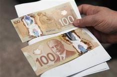 A man holds the new Canadian 100 dollar bills made of polymer in Toronto November 14, 2011. REUTERS/Mark Blinch