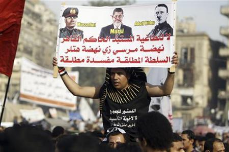 A protester in a Pharaoh headdress holds up a placard during a demonstration on Tahrir Square in Cairo November 30, 2012. REUTERS/Mohamed Abd El Ghany