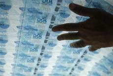 Funcionário verifica notas de cem reais durante na Casa da Moeda do Brasil, no Rio de Janeiro. A economia brasileira cresceu apenas 0,6 por cento no terceiro trimestre deste ano quando comparada com o segundo trimestre, muito abaixo do esperado pelo mercado, com a pior retração dos investimentos em mais de três anos. 23/08/2012 REUTERS/Sérgio Moraes