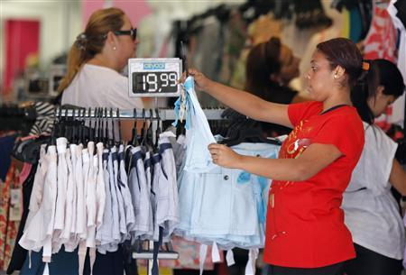 A woman vendor shows a t-shirt inside a shop in Rio de Janeiro November 30, 2012. REUTERS/Sergio Moraes