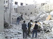 Residents stand among buildings damaged by what activists said were missiles fired by a Syrian Air Force fighter jet loyal to President Bashar al-Assad in Homs November 29, 2012. Picture taken November 29, 2012. REUTERS/Muhammad Al-Ibraheem/Shaam News Network/Handout