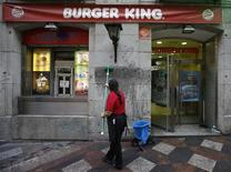 "A woman cleans graffiti reading ""Exploiters"" from the wall of a Burger King restaurant in downtown Madrid November 15, 2012. REUTERS/Andrea Comas"