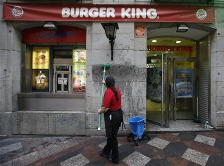 A woman cleans graffiti reading ''Exploiters'' from the wall of a Burger King restaurant in downtown Madrid November 15, 2012. REUTERS/Andrea Comas