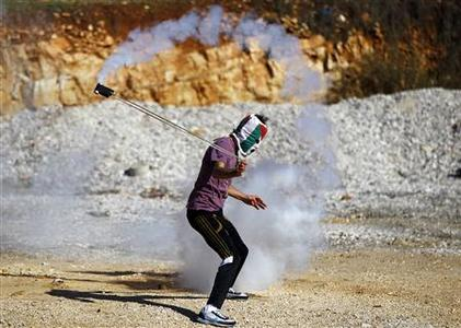 A masked Palestinian stone-throwing protester uses a sling to throw back a tear gas canister fired by Israeli security officers (unseen) during clashes at a protest against Jewish settlements, in the West Bank village of Nabi Saleh, near Ramallah November 30, 2012. REUTERS/Marko Djurica