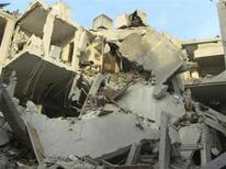 Aviones de la fuerza aérea siria bombardearon el viernes objetivos rebeldes cercanos a la carretera que va al aeropuerto de Damasco y una aerolínea regional dijo que la violencia ha paralizado los vuelos internacionales a la capital. En la imagen, un hombre (abajo a la izquierda) busca pertenencias en un edificio dañado por un caza sirio, según activistas, en la ciudad de Homs el 29 de noviembre. REUTERS/Muhammad Al-Ibraheem/Shaam News Network/Handout