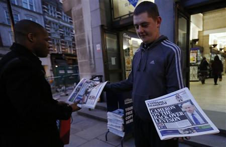A man takes a copy of an evening newspaper, which features an article about Lord Justice Brian Leveson's report on media practices on its front page, from a distributor in central London November 29, 2012 British Prime Minister David Cameron said on Thursday that he had serious concerns about legislation to regulate the media, risking a split in his coalition after a damning inquiry triggered by a phone-hacking scandal proposed a press watchdog backed in law. REUTERS/Olivia Harris