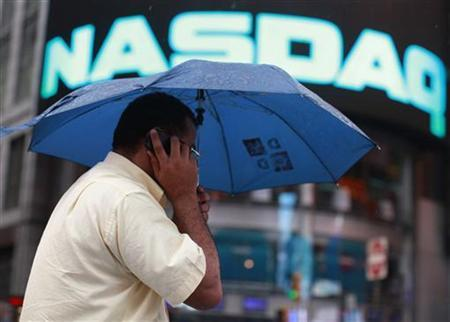 A man walks in the rain outside the Nasdaq Market site in New York's Times Square, July 23, 2012. REUTERS/Brendan McDermid