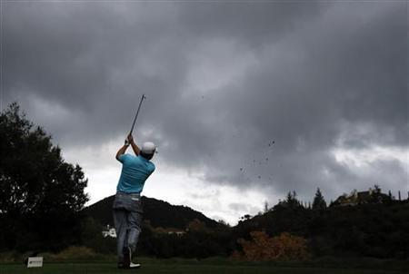 Graeme McDowell of Northern Ireland tees off on the seventeenth hole as storm clouds gather during the second round of the World Challenge golf tournament in Thousand Oaks, California, November 30, 2012. REUTERS/Lucy Nicholson