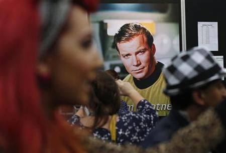 Star Trek fans walk past a poster of actor William Shatner at the Destination Star Trek London convention on October 19, 2012. REUTERS/Suzanne Plunkett/Files