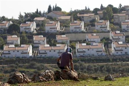 The Jewish settlement of Halamish is seen in the background as a masked Palestinian protester sits on a rock during clashes with Israeli security officers (unseen) at a protest against settlements, in the West Bank village of Nabi Saleh, near Ramallah November 30, 2012. REUTERS/Mohamad Torokman