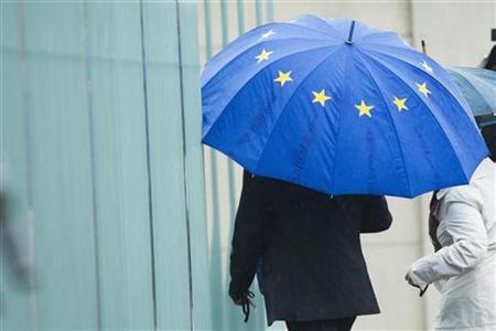 A man holding an umbrella in the colours of the European Union enters the chancellery in Berlin before talks between government and opposition leaders about the EU fiscal pact June 21, 2012. Germany's small Left Party said it would lodge a complaint with the constitutional court in an attempt to prevent ratification of the European Union's fiscal pact, which the Berlin government has championed, and the ESM permanent bailout scheme. REUTERS/Thomas Peter (GERMANY - Tags: POLITICS BUSINESS)