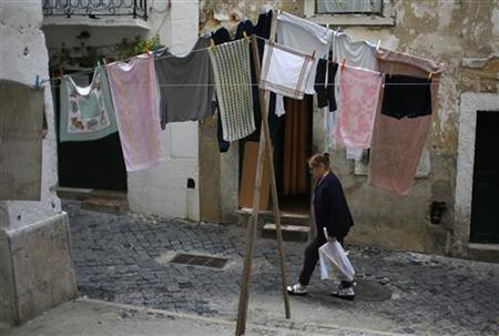 A woman passes by laundry hanging on clotheslines at Alfama neighbourhood in Lisbon November 23, 2012. The top German at the European Central Bank urged his own country on Thursday to compromise in a stand-off over aid to Greece after officials said Finance Minister Wolfgang Schaeuble had hinted at possible debt forgiveness, then backtracked. Members of Merkel's centre-right coalition have said granting Greece debt relief would undermine the reform drive in other struggling euro zone countries such as Portugal. REUTERS/Rafael Marchante (PORTUGAL - Tags: BUSINESS SOCIETY POLITICS)