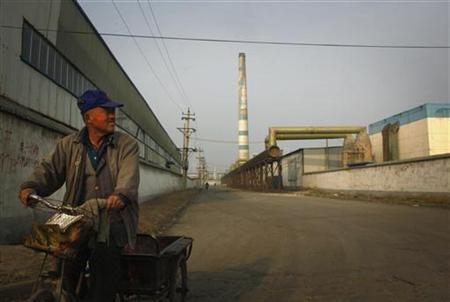 A worker rides a tricycle along a road within the grounds of the huge state-owned lead smelter in the town of Tianying, Anhui Province, November 19, 2012. In ramshackle semi-industrial Tianying in China's Anhui province, a state-owned lead smelter and foundry sits at the centre of town, behind high walls and secure gates that make it look more like a prison than the mainstay of the local economy. Decades of pollution from it and similar plants - Tianying once accounted for half of China's total lead output - has made much of the town's land uninhabitable and its water undrinkable. Picture taken November 19, 2012. To match Feature CHINA-CONGRESS/ENVIRONMENT REUTERS/David Gray (CHINA - Tags: ENVIRONMENT SOCIETY POLITICS)