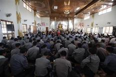 Police pray to Buddhist monks during an apology ceremony at a temple in Monywa December 1, 2012. Riot police fired water cannon and tear gas on Thursday to break up a three-month protest against a copper mining project run by the military-owned Union of Myanmar Economic Holdings Ltd and its partner, a subsidiary of a Chinese arms manufacturer China North Industries Corp. Activists said at least 50 people had been injured and 23 were in hospital, some suffering burns from what activists said were incendiary devices hurled by police. REUTERS/Soe Zeya Tun