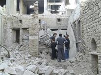 Aviones sirios bombardearon el sábado áreas de Damasco en manos de los rebeldes, dijeron residentes, y el apagón de Internet en todo el país entró en su tercer día. En la imagen, residentes entre edificios destruidos por lo que activistas dijeron fueron misiles disparados por las fuerzas aéreas sirias del presidente Bashar al Asad, en Homs, el 29 de noviembre de 2012. REUTERS/Muhammad Al-Ibraheem/Shaam News Network/Handout